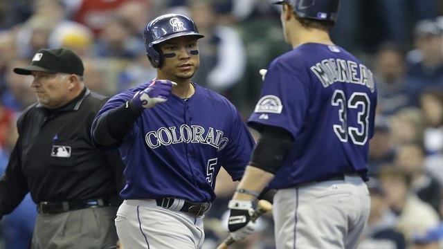 Carlos Gonzalez is greeted by Justin Morneau after his first of two runs.