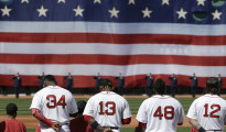 Boston Red Sox's, from the left, Dustin Pedroia (15), David Ortiz (34), Hanley Ramirez (13), Pablo Sandoval (48), and Mike Napoli (12), stand together during the playing of the national anthem before the start of a baseball game against the Washington Nationals, Monday, April 13, 2015, in Boston. (AP Photo/Steven Senne)