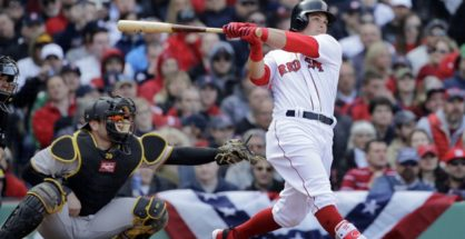 Boston Red Sox's Andrew Benintendi hits a three-run homer in front of Pittsburgh Pirates catcher Francisco Cervelli (29) during the fifth inning of a baseball game at Fenway Park, Monday, April 3, 2017, in Boston. (AP Photo/Elise Amendola)